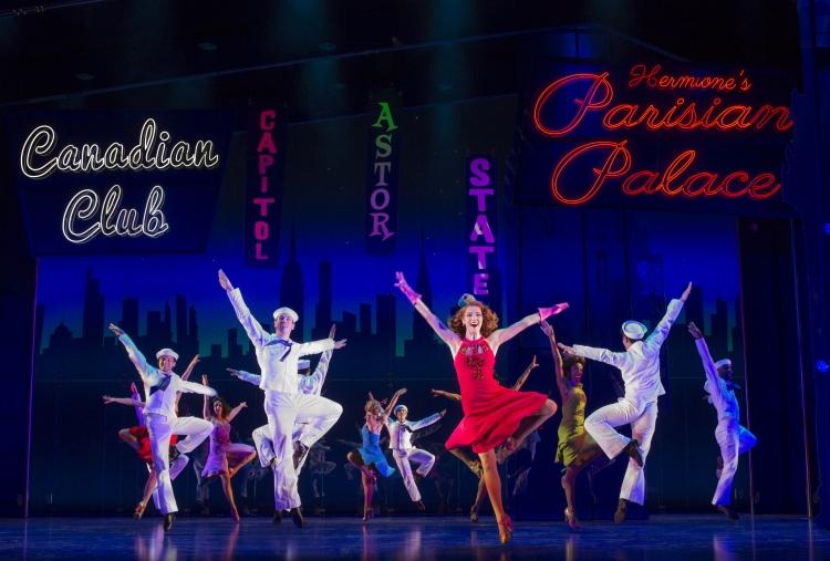 An ensemble cast dances across a theater stage